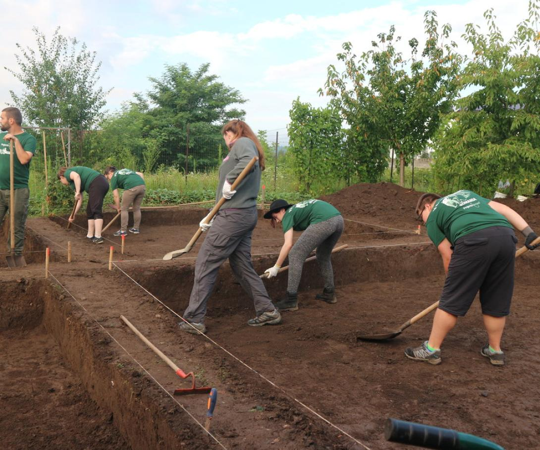 Archaeology volunteers in Romania digging at an excavation site.